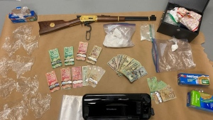Police say they seized 300 grams of cocaine packaged in both bulk form and for distribution, $7,865 in cash and a Winchester rifle. (Credit: Saskatoon Police Service)