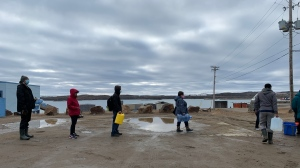 Residents line up to fill containers with potable water in Iqaluit, Nunavut on Thursday, Oct. 14, 2021.THE CANADIAN PRESS/Emma Tranter