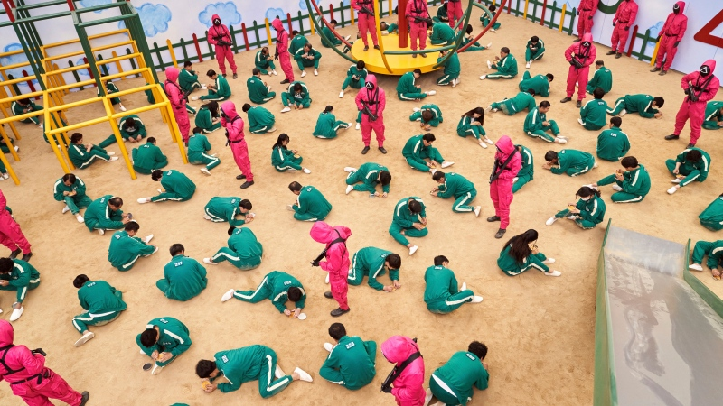 """This undated photo released by Netflix shows a scene of contestants vying to win the Dalgona Korean candy challenge in a scene from """"Squid Game."""" (Youngkyu Park/Netflix via AP)"""