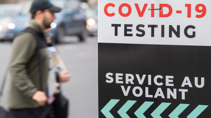 A man walks by a sign for a COVID-19 testing centre in Montreal, Sunday, October 10, 2021, as the COVID-19 pandemic continues in Canada and around the world. THE CANADIAN PRESS/Graham Hughes