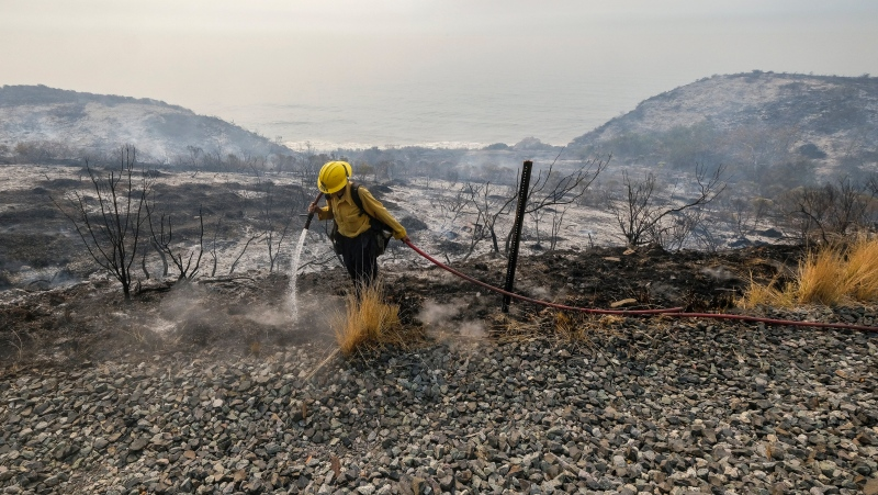 County of Santa Barbara Fire Department firefighters extinguish a roadside fire next to train tracks off of the U.S. 101 highway Wednesday, Oct. 13, 2021, in Goleta, Calif. (AP Photo/Ringo H.W. Chiu)