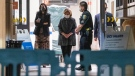 Former U.S. Secretary of State Hillary Clinton, middle, exits the University of California Irvine Medical Center in Orange, Calif., Thursday, Oct. 14, 2021. (AP Photo/Damian Dovarganes)