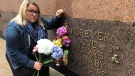 Chantelle Meadows holds flowers next her daughter's burial site at Heavenly Rest cemetery, Oct. 15, 2021. (Alana Hadadean / CTV News)