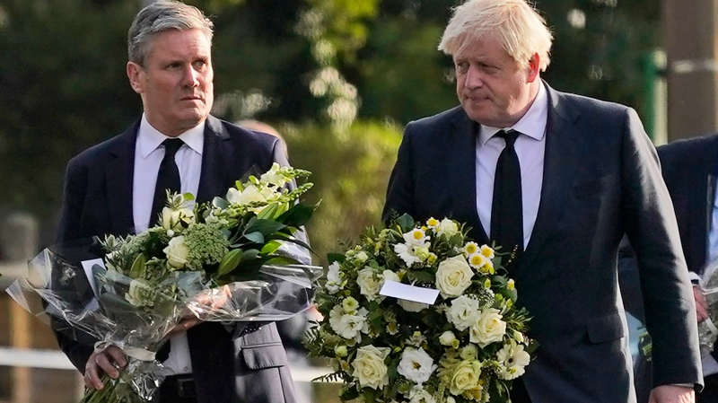 British Prime Minister Boris Johnson, right, and Leader of the Labour Party Keir Starmer carry flowers as they arrive at the scene where a member of Parliament was stabbed Friday, in Leigh-on-Sea, Essex, England, Saturday, Oct. 16, 2021. (AP Photo/Alberto Pezzali)