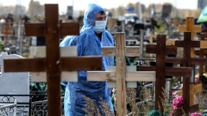 A grave digger wearing a protective suit stands during a a COVID-19 victim burial at a cemetery outside in Omsk, Russia, Thursday, Oct. 7, 2021.  (AP Photo)
