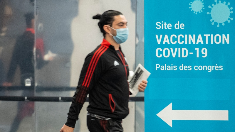 A man wears a face masks as he walks by a COVID-19 vaccination sign in Montreal, Sunday, October 10, 2021, as the COVID-19 pandemic continues in Canada and around the world. THE CANADIAN PRESS/Graham Hughes