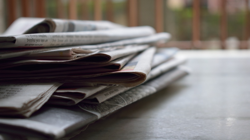 A pile of newspapers is seen in this stock image. (Pexels)