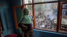 A Kashmiri woman watches as villagers stand on the debris of a house destroyed in a gunfight in Pampore, south of Srinagar, Indian controlled Kashmir, Saturday, Oct. 16, 2021. Indian government forces killed five rebels in last 24-hours in disputed Kashmir on Saturday, officials said, as violence increased in recent weeks. (AP Photo / Dar Yasin)