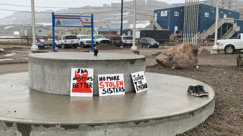 People placed signs, a pair of shoes and a candle outside the Iqaluit RCMP detachment on Thursday, June 3, 2021, during a walk calling for justice for Nunavut actress Emerald MacDonald, who was found dead outside Kugluktuk on May 3. (THE CANADIAN PRESS / Emma Tranter)