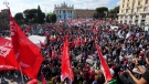 Demonstrators take part in a march organized by Italy's main labor unions, in Rome's St. John Lateran square, Saturday, Oct. 16, 2021. The march was called a week after protesters, armed with sticks and metal bars, smashed their way into the headquarters of CGIL, a left-leaning union, and trashed its office, during a demonstration to protest a government rule requiring COVID-19 vaccines or negative tests for workers to enter their offices. (AP Photo/Andrew Medichini)