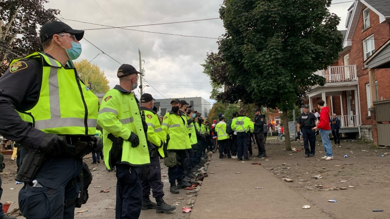 Dozens of police officers stand along Aberdeen Street after Kingston police declared an aggravated nuisance party, ordering people to disperse. (Kimberley Johnson/CTV News Ottawa)