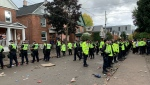 More than 50 police officers line Aberdeen Street in Kingston to break-up a large gathering during homecoming weekend at Queen's University. (Kimberley Johnson/CTV News Ottawa)