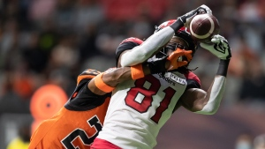 Calgary Stampeders' Luther Hakunavanhu (81) makes a touchdown reception as B.C. Lions' Jalon Edwards-Cooper defends during the first half of a CFL football game in Vancouver, on Saturday, October 16, 2021. (THE CANADIAN PRESS/Darryl Dyck)
