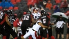 Ottawa Redblacks quarterback Caleb Evans (5) throws the ball as he gets tackled by Montreal Alouettes defensive lineman Jamal Davis II (99) during first half CFL football action in Ottawa on Saturday, Oct. 16, 2021. (THE CANADIAN PRESS/Justin Tang)