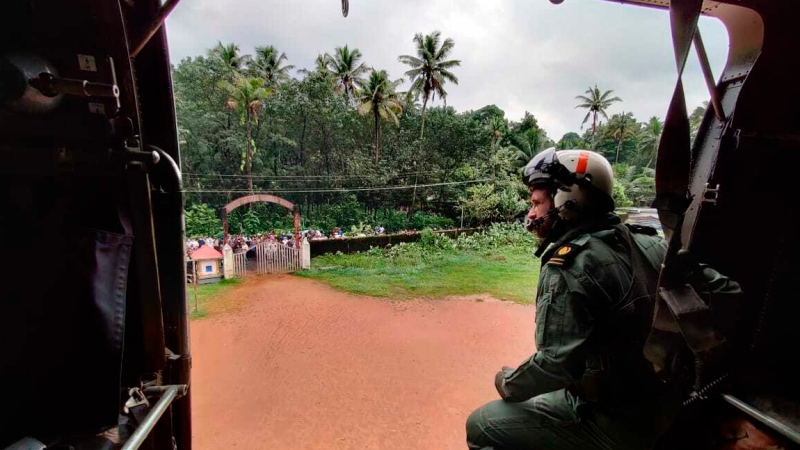This photograph provided by the Indian Navy shows a navy person looking from their helicopter on a mission to distribute relief material to flood affected people at Koottickal in Kottayam district, southern Kerala state, India, Sunday, Oct.17, 2021. Rescue operations were underway on Sunday after heavy rains lashed the state the day before, triggering flash floods and landslides across districts. (Indian Navy via AP)