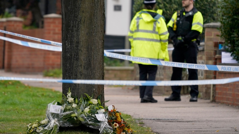 Flowers laid by Labour Party leader Keir Starmer, Prime Minister Boris Johnson, Speaker of the House Lindsay Hoyle and British Home Secretary Priti Patel lie at the foot of a tree by the scene where a member of Parliament was killed on Friday, at the Belfairs Methodist Church, in Leigh-on-Sea, Essex, England, Saturday, Oct. 16, 2021. (AP Photo/Alberto Pezzali)