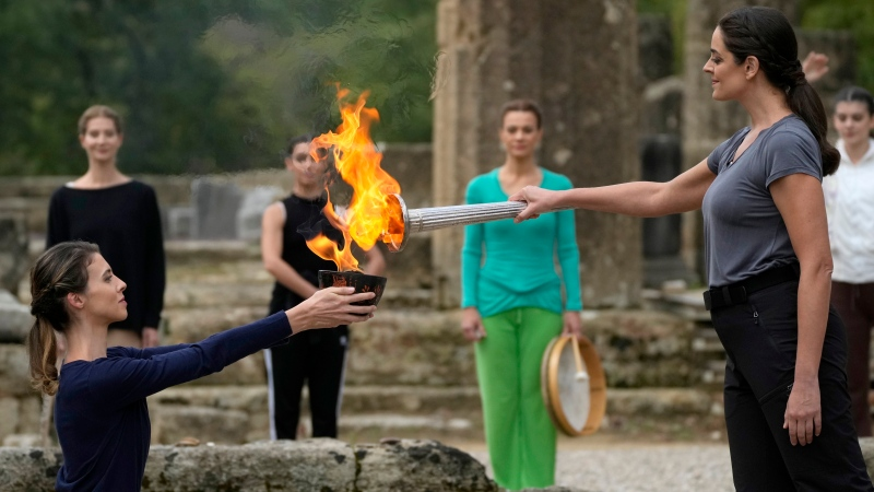 Greek actress Xanthi Georgiou, right, playing the role of the High Priestess, lights the torch during the final rehearsal for the lighting of the Olympic flame at Ancient Olympia site, birthplace of the ancient Olympics in southwestern Greece, Sunday, Oct. 17, 2021. The flame will be transported by torch relay to Beijing, China, which will host the Feb. 4-20, 2022 Winter Olympics. (AP Photo/Thanassis Stavrakis)