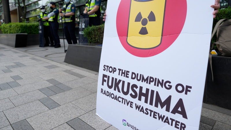 A member of civic group holds a sign demanding the withdrawal of Japanese government's decision to release treated radioactive water from the Fukushima Daiichi nuclear power plant damaged in the 2011 earthquake and tsunami, near a building which houses Japanese Embassy in Seoul, South Korea, Wednesday, June 2, 2021. (AP Photo/Lee Jin-man)