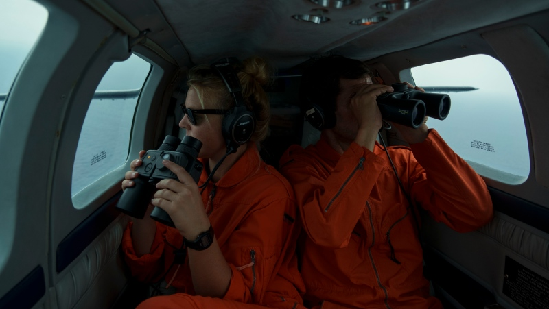 German volunteers Leona Blankenstein, left, and David Lohmueller search from aboard the Seabird, a humanitarian monitoring aircraft, for migrant boats in distress as they fly over the Mediterranean Sea between Libya and the Italian island of Lampedusa, Tuesday, Oct. 5, 2021.  (AP Photo/Renata Brito)