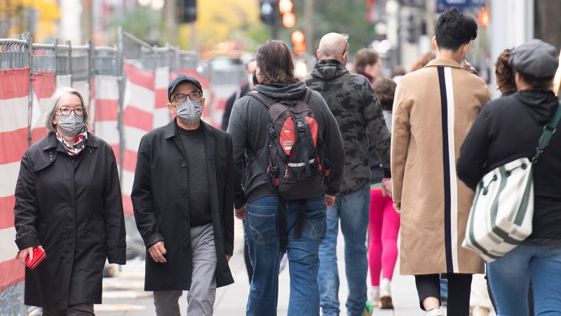 People wear face masks a they walk along a street in Montreal, Sunday, October 10, 2021, as the COVID-19 pandemic continues in Canada and around the world. THE CANADIAN PRESS/Graham Hughes