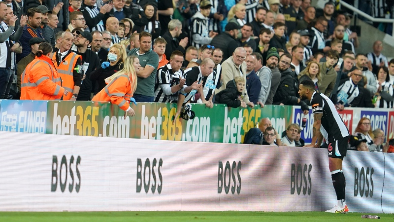 Newcastle's Jamaal Lascelles asks about a person with a possible medical problem in the crowd during an English Premier League soccer match between Newcastle and Tottenham Hotspur at St. James' Park in Newcastle, England, Sunday Oct. 17, 2021. (AP Photo/Jon Super)