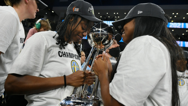 Chicago Sky's Diamond DeShields, left, and Lexie Brown, right, celebrate with the trophy after defeating the Phoenix Mercury 80-74 in Game 4 of the WNBA Finals to become the 2021 WNBA champions, Sunday, Oct. 17, 2021, in Chicago. (AP Photo/Paul Beaty)