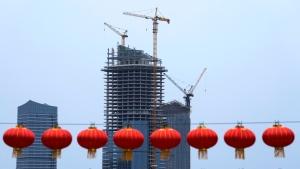 Red lanterns hang in front of a commercial office buildings under construction in Tongzhou, on the outskirts of Beijing, Monday, Oct. 4, 2021. (AP Photo/Andy Wong)