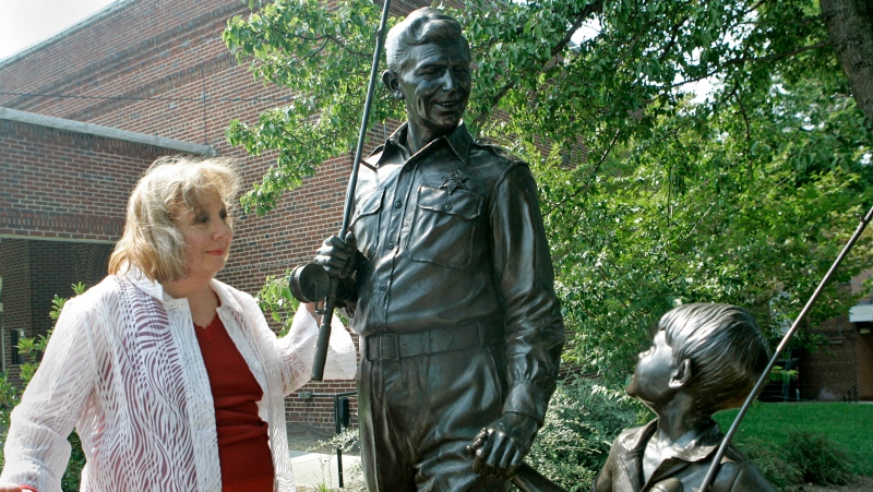 """In this Sept. 6, 2007 file photo, actor Betty Lynn, who played Thelma Lou on """"The Andy Griffith Show,"""" pauses at a statue of Andy and Opie Taylor in Mount Airy, N.C. (AP Photo/Gerry Broome, File)"""