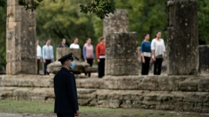 An officer wearing a face mask watches as actresses perform during the final rehearsal for the lighting of the Olympic flame at Ancient Olympia site, birthplace of the ancient Olympics in southwestern Greece, Sunday, Oct. 17, 2021. (AP Photo/Petros Giannakouris)
