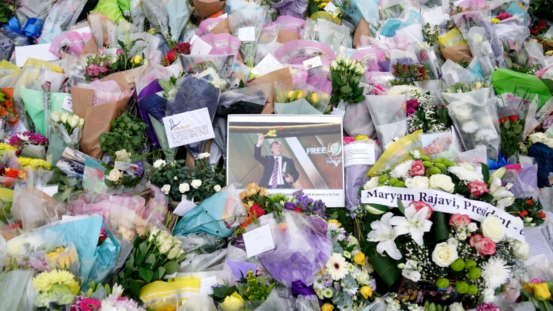 A photograph of member of Parliament David Amess is seen among the flower tribute near the Belfairs Methodist Church in Eastwood Road North, where Amess died after he was stabbed several times on Friday, in Leigh-on-Sea, Essex, England, Sunday, Oct. 17, 2021. (Kirsty O'Connor/PA via AP)