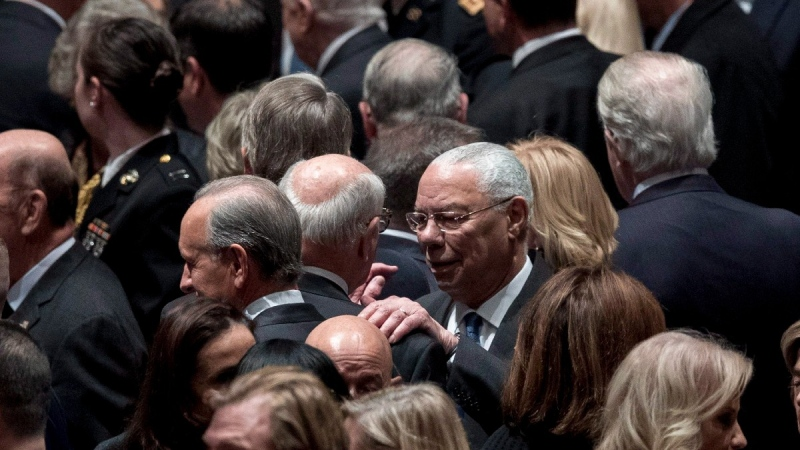 Former U.S. Secretary of State Colin Powell, centre right, speaks to a guest before a State Funeral for former President George H.W. Bush at the National Cathedral in Washington, on Dec. 5, 2018. (Andrew Harnik / AP)
