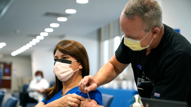 Registered nurse Alix Zacharski, left, receives a Pfizer COVID-19 booster shot from Douglas Houghton, right, at Jackson Memorial Hospital Tuesday, Oct. 5, 2021, in Miami. (AP Photo/Lynne Sladky)