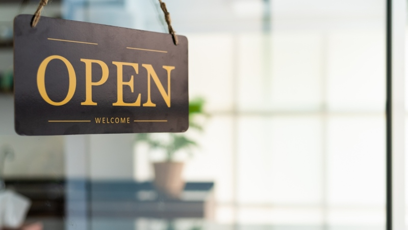 An open sign hangs in the window of a business. (Getty Images)