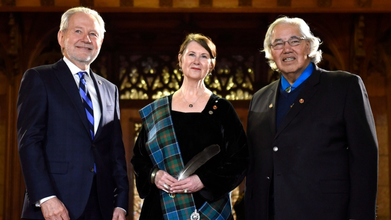 Marilou McPhedran (centre) stands with Senator Peter Harder (left) and Senator Murray Sinclair before being sworn in during a ceremony in the Senate on Parliament Hill, Wednesday, Nov. 16, 2016 in Ottawa. (THE CANADIAN PRESS/Justin Tang)