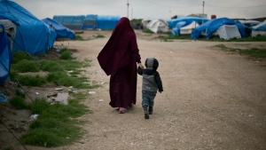 In this March 27, 2019, photo, Samira from Belgium walks with her son at Camp Roj in north Syria.  (AP Photo/Maya Alleruzzo)