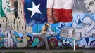 A man adjusts his face mask as he walks past a mural in the heavily Latino section of Oak Cliff in Dallas, Wednesday, Sept. 22, 2021. (AP Photo/LM Otero)