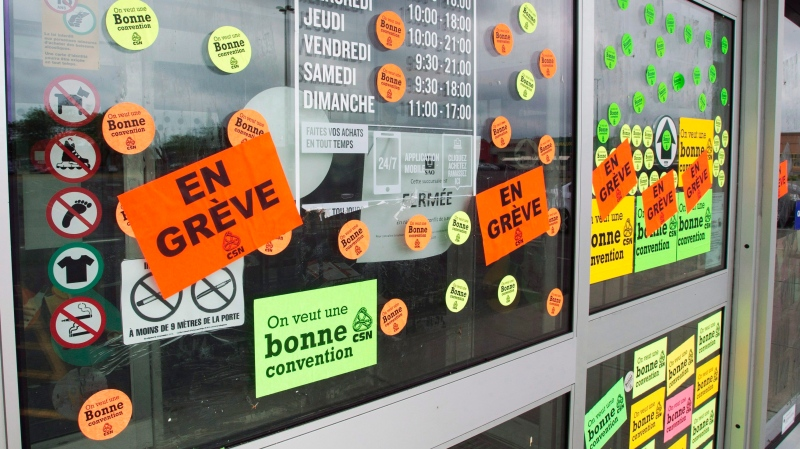Stickers cover the entrance to an SAQ outlet as liquor store employees go on strike to press lagging contract negotiations, Tuesday, July 17, 2018 in St. Marthe-sur-le-Lac Que.THE CANADIAN PRESS/Ryan Remiorz