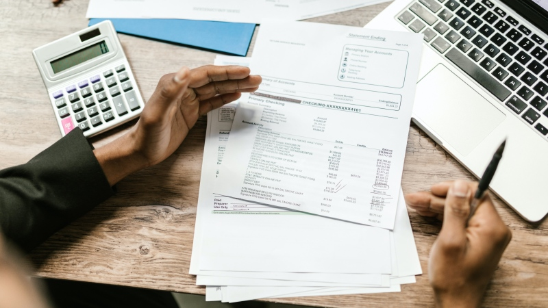 A man looks at his bills in this stock photo. (RODNAE Productions/Pexels)
