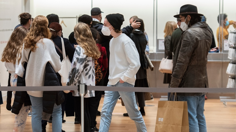 People wear face masks a they shop at a clothing store in Montreal, Sunday, October 10, 2021, as the COVID-19 pandemic continues in Canada and around the world. THE CANADIAN PRESS/Graham Hughes