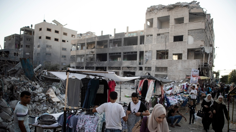 In this Sunday, July 18, 2021, file photo, Palestinian street vendors display clothes for sale next to the rubble of destroyed buildings were hit by Israeli airstrikes during an 11-day war between Gaza's Hamas rulers and Israel, in Gaza City. (AP Photo/Khalil Hamra, File)