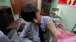 FILE- A student receives a doze of Pfizer COVID-19 vaccine from a health worker at a school in Lahore, Pakistan, Saturday, Oct. 2, 2021. (AP Photo/K.M. Chaudary)
