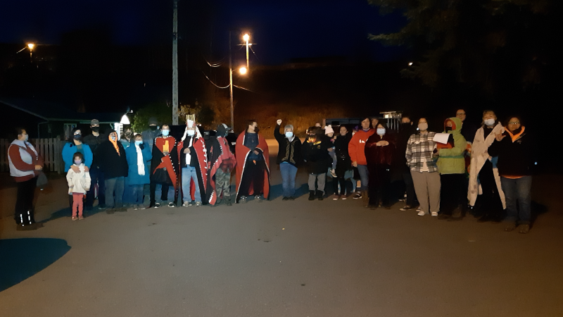 A line of band councillors, hereditary chiefs and community members standing together near Gitanmaax, refusing to let the social workers take away a six-year-old Gitanmaax band member. (Photo source: Git'luuhl'um'hetxwit Media).