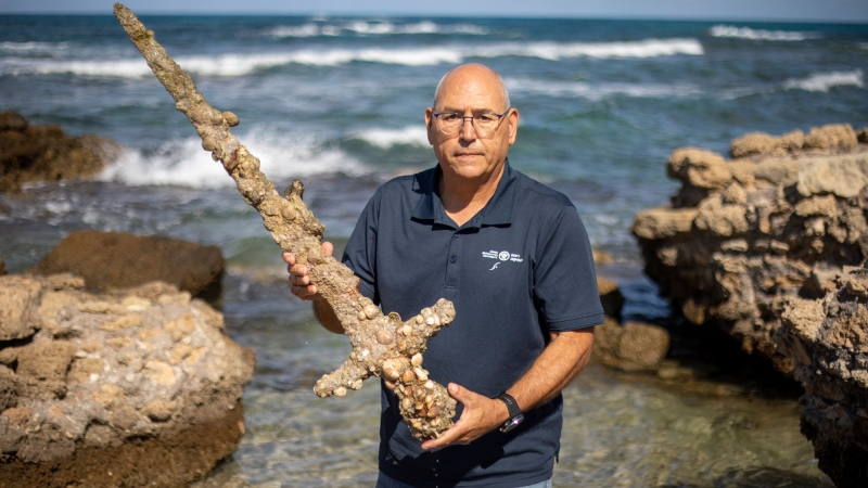 Jacob Sharvit, director of the Marine Archaeology Unit of the Israel Antiquities Authority holds a meter-long (yard-long) sword that experts say dates back to the Crusaders, Tuesday, Oct. 19, 2021, in Mediterranean seaport of Cesarea, Israel. Israeli archaeologists say a scuba diver spotted the ancient sword, along with other ancient artifacts, including anchors and pottery, during a dive on Saturday. (AP Photo/Ariel Schalit)