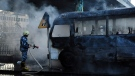 In this photo released by the Syrian official news agency SANA, a Syrian firefighter extinguishes a burned bus at the site of a deadly explosion, in Damascus, Syria, Wednesday, Oct. 20, 2021. (SANA via AP)