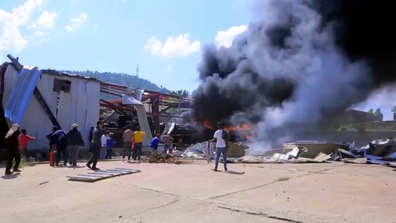 In this image made from video, people look on as a car factory burns in Mekele, Ethiopia, Wednesday, Oct. 20, 2021. (AP Photo)