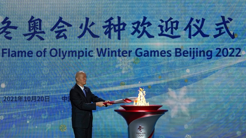 Cai Qi, Beijing Communist Party secretary lits up the Olympic cauldron during a welcome ceremony for the Frame of Olympic Winter Games Beijing 2022, held at the Olympic Tower in Beijing, Wednesday, Oct. 20, 2021. (AP Photo/Andy Wong)