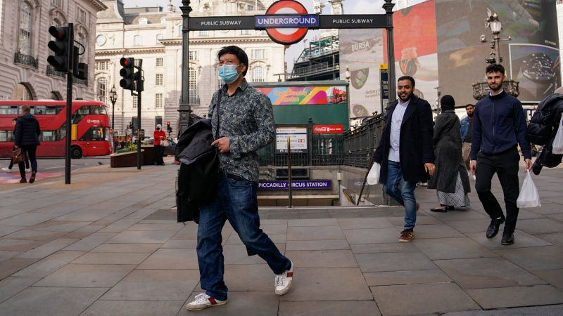 A man wears a face mask as he walks in Piccadilly Circus, in London, Tuesday, Oct. 19, 2021. (AP Photo/Alberto Pezzali)