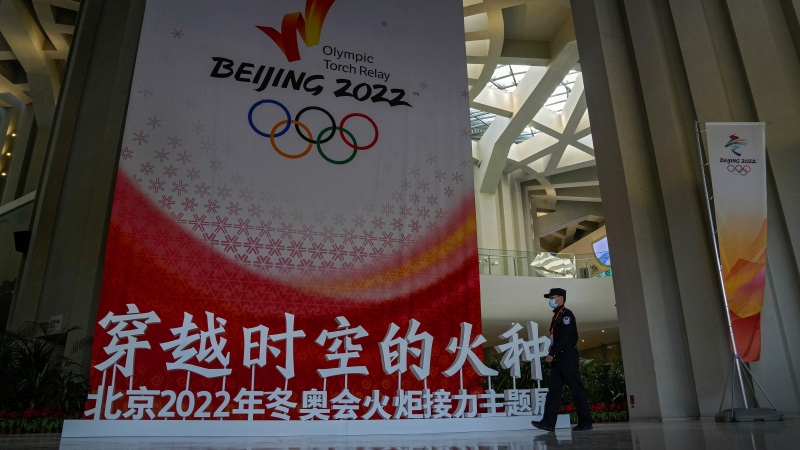 A security guard wearing a face mask to help curb the spread of the coronavirus patrols past a Beijing 2022 Winter Olympic Games decoration in Beijing, Wednesday, Oct. 20, 2021. (AP Photo/Andy Wong)