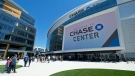 FILE - In this Aug. 26, 2019, file photo, people walk outside the Chase Center in San Francisco. (AP Photo/Eric Risberg, File)