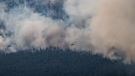 A helicopter pilot flies past a wildfire burning in Lytton, B.C., on Thursday, July 1, 2021. THE CANADIAN PRESS/Darryl Dyck